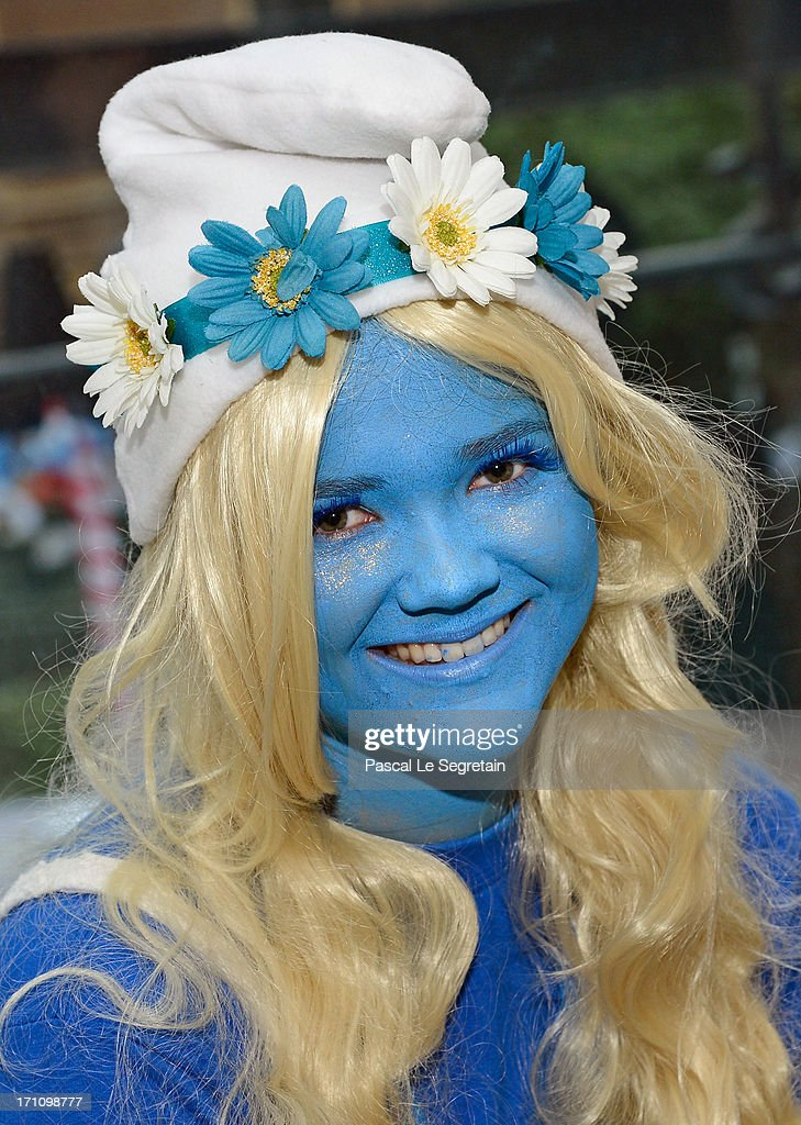 A Smurf Ambassador dressedup as a Smurf character poses during a ceremony as part of Global Smurfs Day celebrations on June 22, 2013 in Brussels, Belgium. A giant Smurf figurine is seen behind.
