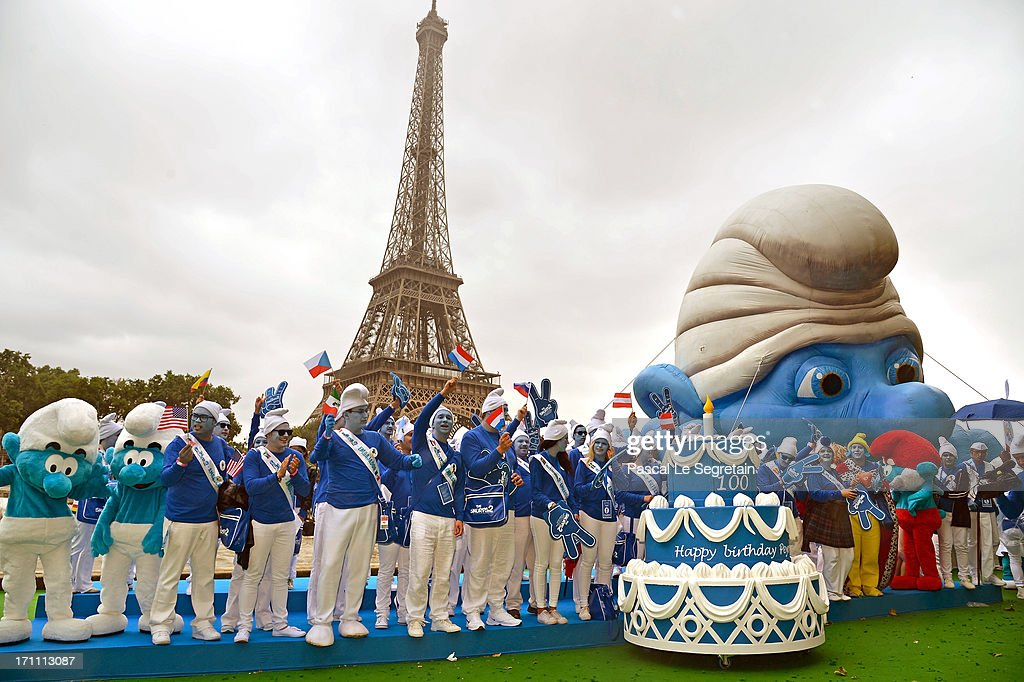 Smurf Ambassadors pose by a giant Smurf character as part of Global Smurfs Day celebrations on June 22, 2013 on the Seine river bank in Paris, France. The Eiffel tower is seen behind.