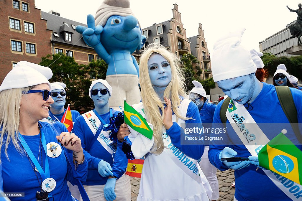 Smurf Ambassadors pose for a group photo below a giant Smurf character on Place d'Espagne as part of Global Smurfs Day celebrations on June 22, 2013 in Brussels, Belgium.