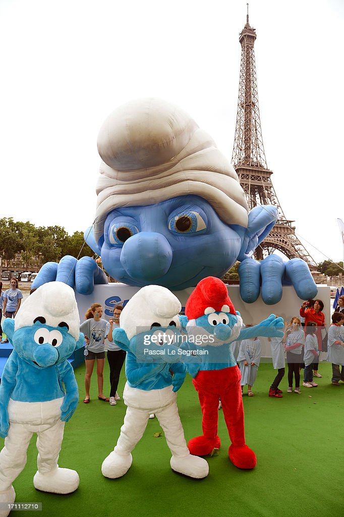 Smurf characters pose by a giant Smurf character as part of Global Smurfs Day celebrations on June 22, 2013 on the Seine river bank in Paris, France.