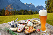 A fresh snack with different kinds of spreads on farmhouse bread served with a fresh yeast wheat beer on an old wooden table in the Bavarian Alps near to Garmisch-Partenkirchen.