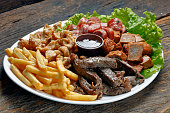 Snacks with fries, crackers, meat, pork, sausage and babercue sauce