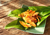 Slices of preserved mango,sweet and sour dessert from Cebu,Philippines.Served on green leaves and placed on rustic wood background.