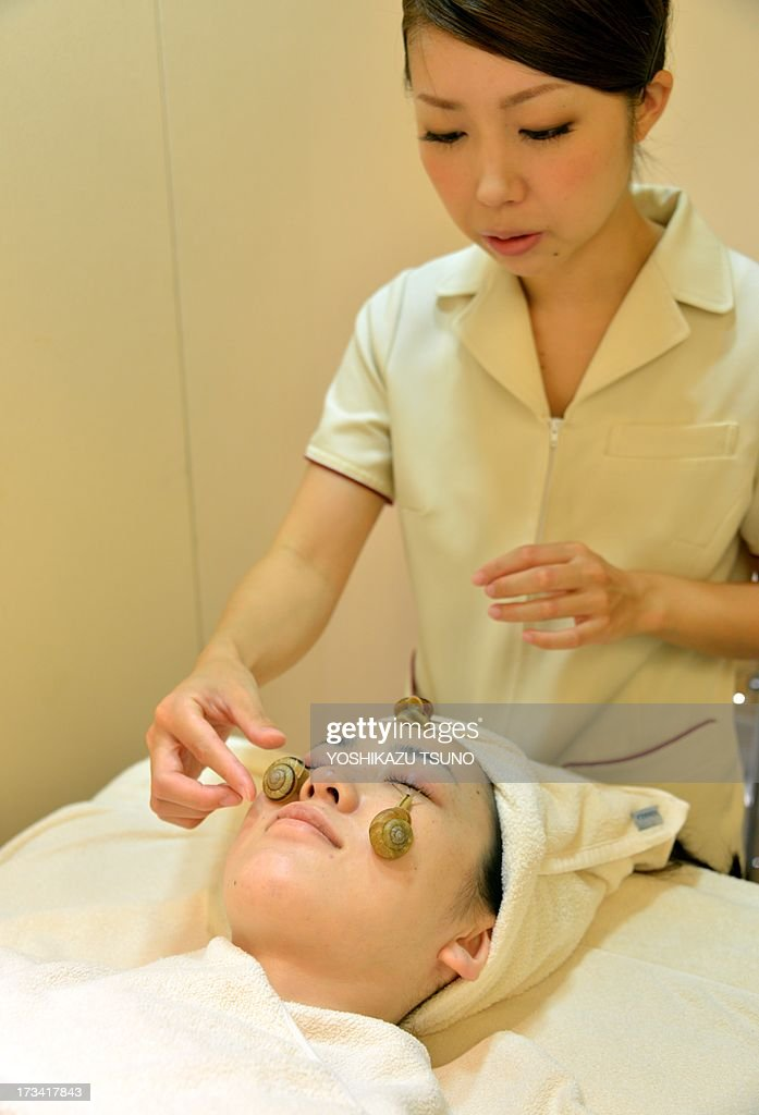Snails crawls on the face of a woman for the demonstration of a new beauty treatment at the beauty salon 'Ci:z.Labo' in Tokyo on July 13, 2013 as the salon will start the new service from July 15. 'Slime from snails helps remove old cells, heal the skin after sun burn and moisturise it,' said Manami Takamura (R), a beauty salon employee, as she placed three gastropods on a woman's face. AFP PHOTO / Yoshikazu TSUNO