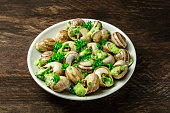 A photo of escargots a la bourguignonne, a plate of snails with the typical French green sauce of garlic and herb butter, on a rustic texture with a place for text