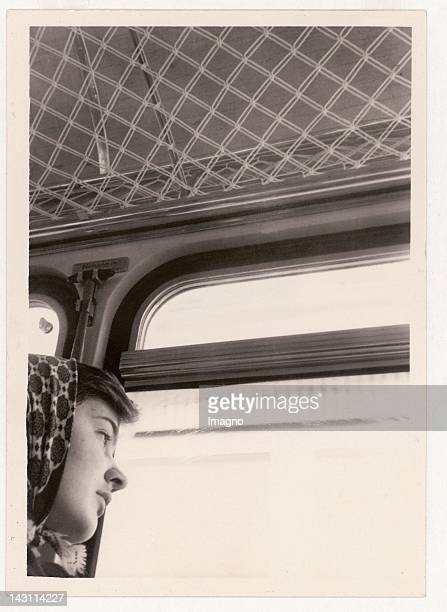 Snapshot Girl with headscarf looking out of the window of a train in a melancholy way Austria 1950s