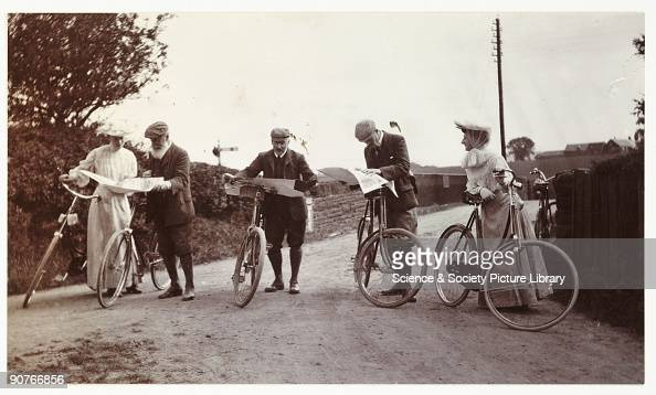 A snapshot photograph of a group of cyclists on a country road consulting their maps taken by an unknown photographer in about 1906 A craze for...