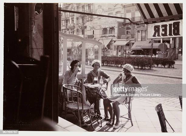 A snapshot photograph of a group of women relaxing in a French pavement cafe taken by an unknown photographer in about 1930 An older woman and two...