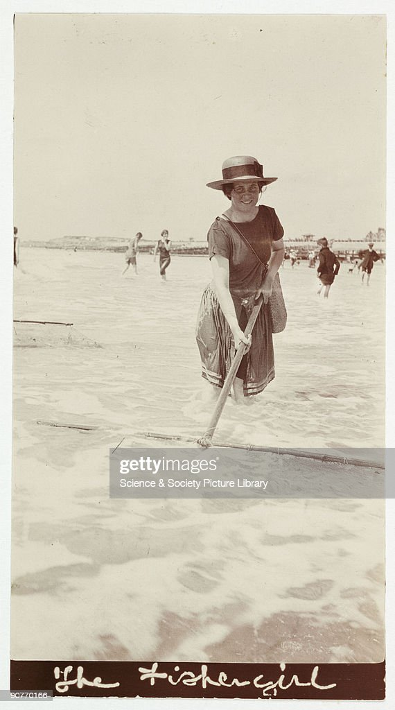 A snapshot photograph of a woman at the seaside, taken by an unknown photographer in about 1918. A woman trawls the surf for shrimps, a popular seaside delicacy. This photograph was taken using an Autographic Kodak Junior camera. First introduced in 1914, the camera included a stylus with which the user could 'write' onto the film backing paper. The Autographic feature was used on all popular Kodak cameras, except for the Brownie box cameras, until the early 1930s. Originally a shooting term, the word 'snapshot' was first linked with photography in the late 1850s, when it was used to describe a photograph taken with a brief exposure. Over time, snapshot came to mean any amateur photograph taken with a simple camera.