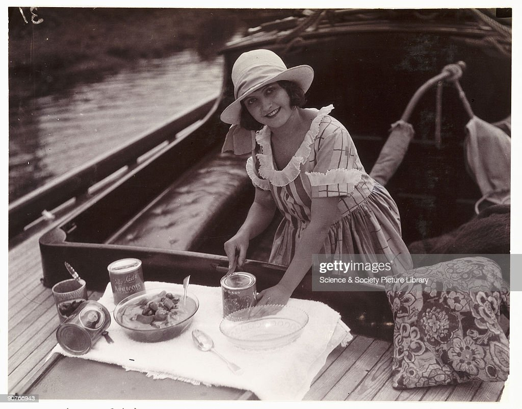 A snapshot photograph of a woman opening tins of �My Lady� apricots on a boat taken by an unknown photographer in about 1925 Originally a shooting...