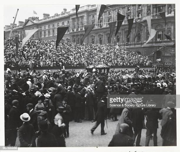 A snapshot photograph of crowds lining a London street during the coronation procession of King Edward VII The royal carriage can just be seen above...