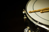 A snare drum and a pair of drumsticks.