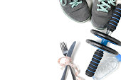 Sneakers and fitness wheel with knife and fork wrapped in tape measure isolated on white background, diet and exercise to lose weight concept