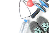 Sneakers and fitness wheel with stethoscope isolated on white background, diet and exercise to lose weight concept