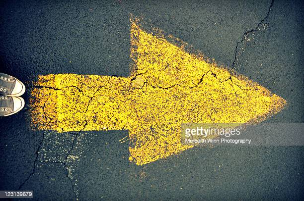 Sneakers and yellow arrow painted on asphalt