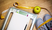 Sneakers, centimeter, green apple, notebook, scale. Weight loss,  healthy lifestyle concept