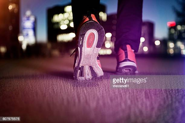 Sneakers of jogging man on tarmac at night