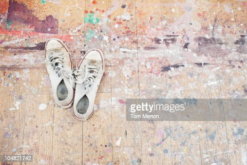 Sneakers on paint-spattered wood floor