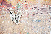 Sneakers on paint-spattered wood floor