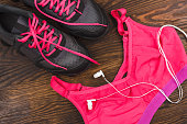 Pair of sneakers, shorts and sports bra, wooden background