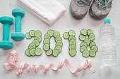 Sneakers, towel, water and dumbbells. Cucumber sliced symbol of the new year. Diet 2018.