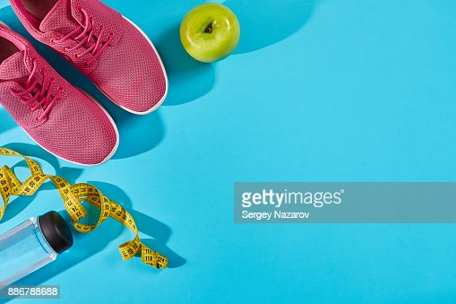 Sneakers with measuring tape on cyan blue background. Centimeter in yellow color near pink trainers, close up : Stock Photo