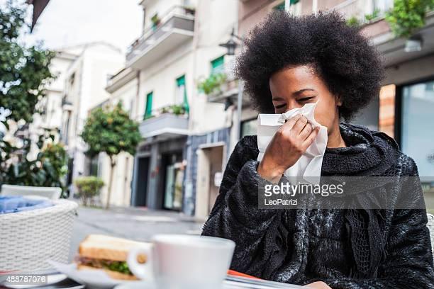Niesen aufgrund der Grippe in eine Pause in einem Café