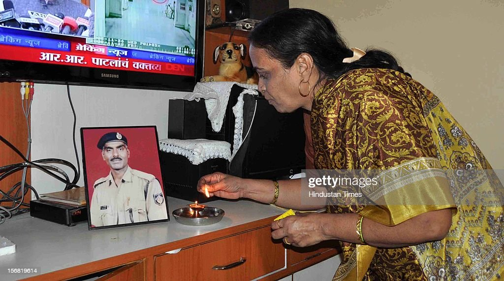 Snehalata wife of 26/11 Martyr Head Constable Murlidhar Choudhary lights the lamp in front of his picture to celebrate the news of Ajmal Kasab's hanging on November 21, 2012 in Mumbai, India. Terrorist Ajmal Kasab sentenced to death for his role in November 26, 2008 terror attack on Mumbai was hanged to death at Yerwada Jail on November 21, 2012 in Pune, India.