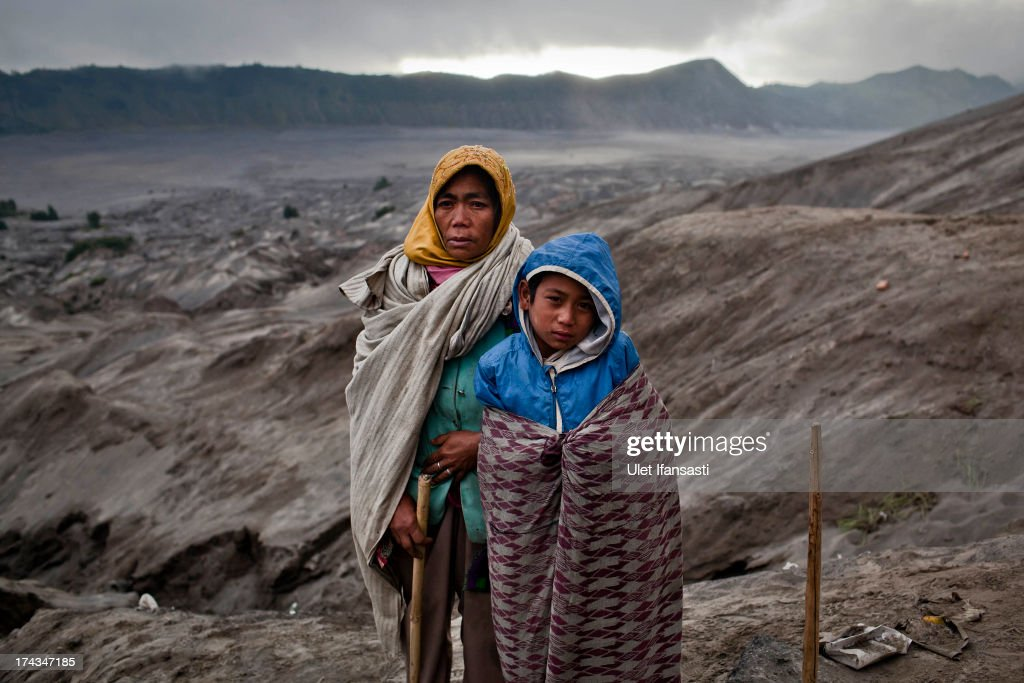 Snepi, with his son, Doni, stand at foot of Mount Bromo during the Yadnya Kasada Festival at crater of Mount Bromo on July 24, 2013 in Probolinggo, East Java, Indonesia. The festival is the main festival of the Tenggerese people and lasts about a month. On the fourteenth day, the Tenggerese make the journey to Mount Bromo to make offerings of rice, fruits, vegetables, flowers and livestock to the mountain gods by throwing them into the volcano's caldera. The origin of the festival lies in the 15th century when a princess named Roro Anteng started the principality of Tengger with her husband Joko Seger, and the childless couple asked the mountain Gods for help in bearing children. The legend says the Gods granted them 24 children but on the provision that the 25th must be tossed into the volcano in sacrifice. The 25th child, Kesuma, was finally sacrificed in this way after initial refusal, and the tradition of throwing sacrifices into the caldera to appease the mountain Gods continues today.