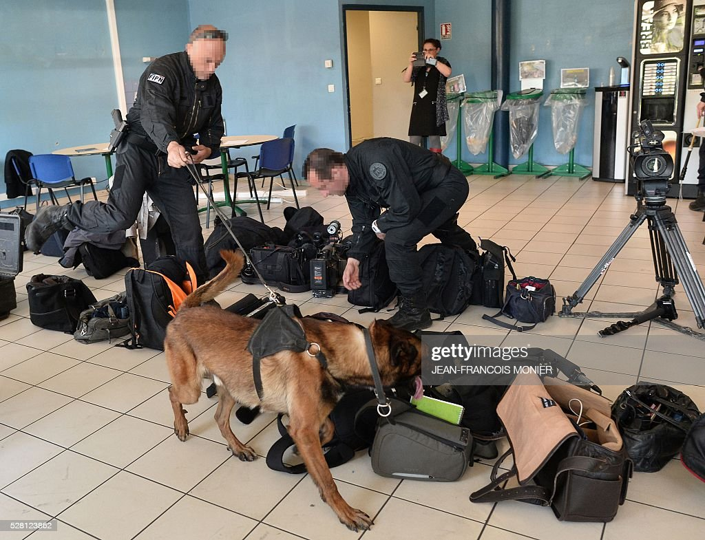 A sniffer dog inspects the bags containing journalists' equipment prior to the start of a press conference by French president during his visit to the Mecachrome's group MK Automotive plant, on May 4, 2016 in Sable-sur-Sarthe, west France. / AFP / JEAN