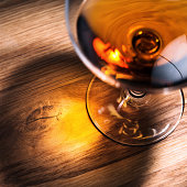 snifter with brandy on old oak table, focus on table