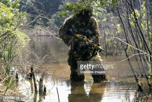 A sniper dressed in a ghillie suit crosses a stream while on patrol. : Foto de stock