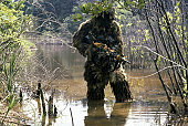 A Marine sniper team member wearing a camouflage ghillie suit crosses a stream while on a training patrol at the Marine Corps Development and Education Command.