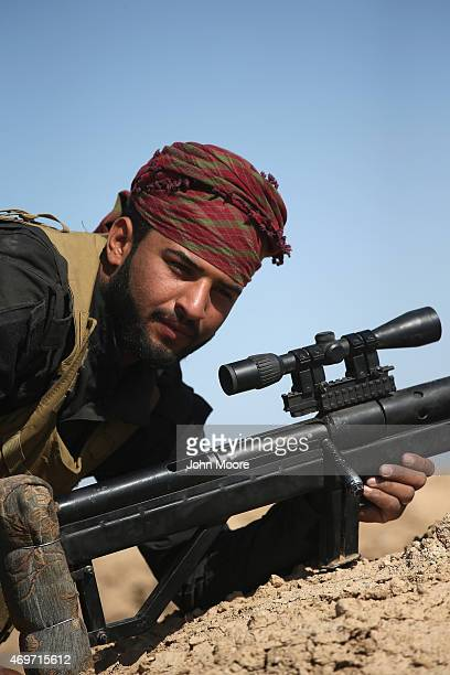 A sniper from the Abu al Fadhel al Abbas militia takes a frontline position in support of Iraqi Army troops as they assault ISIL fighters on April 14...