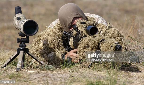 A sniper of the Ukrainian National Guard takes part in a military training at the National Guard training center in the village of Stare some 70 km...