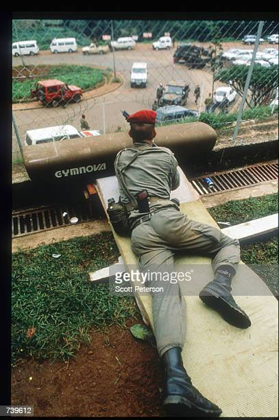 A sniper protects a French school as it is evacuated April 11 1994 in Kigali Rwanda The majority of French and Belgian nationals living in Rwanda...