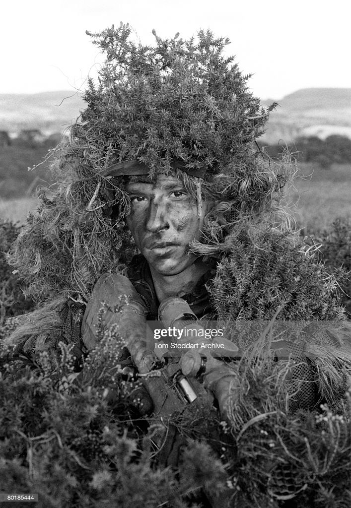 A sniper wearing a ghillie suit and camouflage during training at the Royal Marines Commando Training Centre in Lympstone, Devon, October 2007.