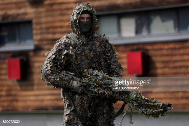 A GIGN sniper wears camouflage and holds a rifle during a visit by the French Interior minsiter at the headquarters of the National Gendarmerie...