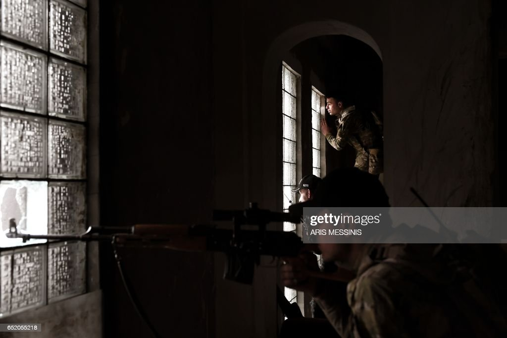 Snipers of the Iraqi troops aim towards Islamic State (IS) jihadists from a inside the museum in west Mosul on March 11, 2017 as the ongoing battle to retake the city from the group continues. /