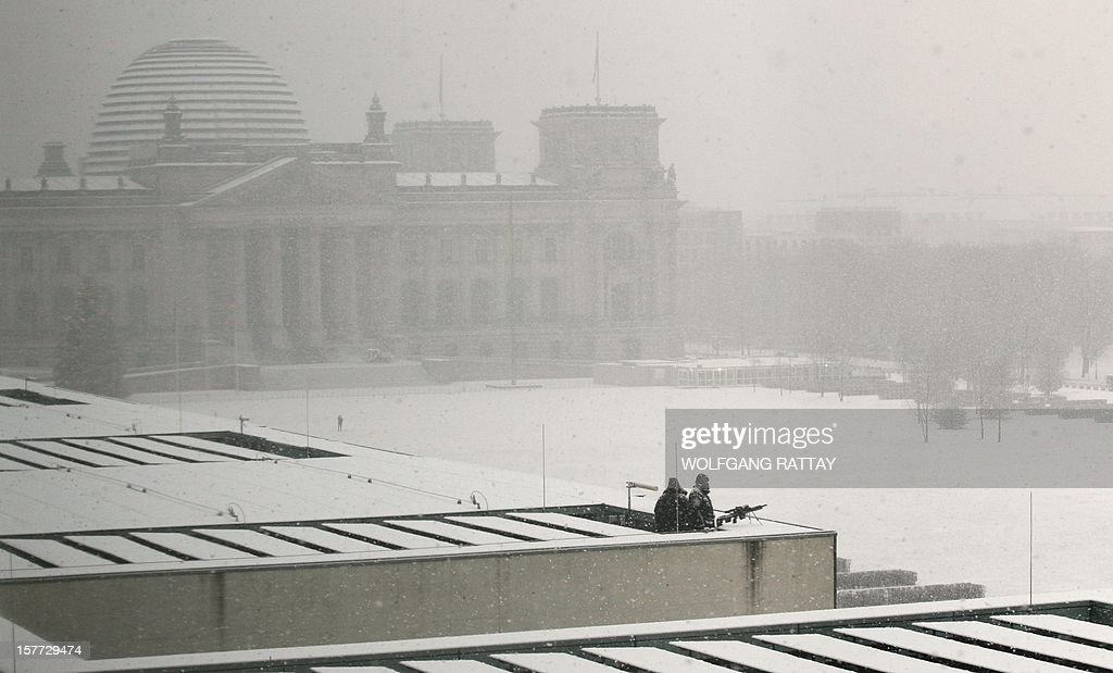 Snipers watch the motorcade of Israeli Prime Minister from the rooftop of the Chancellery during heavy snow fall in Berlin on December 6, 2012, as he arrives for bilateral talks with German Chancellor. Background left is the Reichstag, the seat of Germany's lower house of parliament Bundestag. Netanyahu holds tense talks with German Chancellor Angela Merkel as plans to build thousands of new Jewish settler homes severely strain ties with key allies.