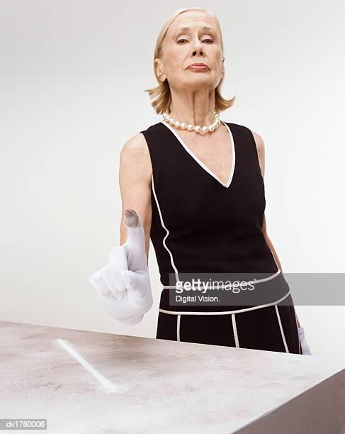 Snobby Senior Woman Showing Dirt on Her White Glove