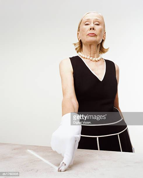 Snobby Senior Woman Wearing a White Glove Pointing to Dirt