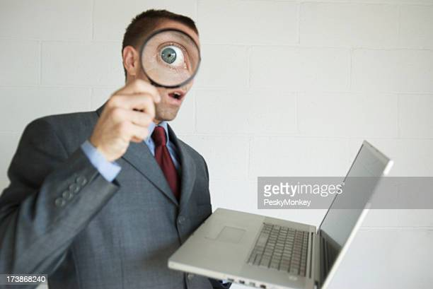 Snooping Businessman Invading Privacy on Laptop with Magnifying Glass