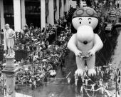 Snoopy breezes by Ol' Chris Columbus statue as thousands cheer watching him in the Macy's Thanksgiving Day Parade