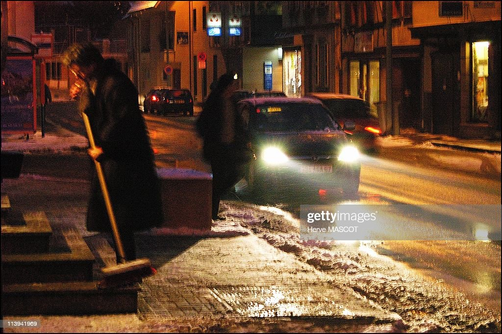 Snow and cold weather in eastern France, On January 26, 2006-Erstein, night sweeping, a woman removed the snow from her door steps in the Bas Rhin region.