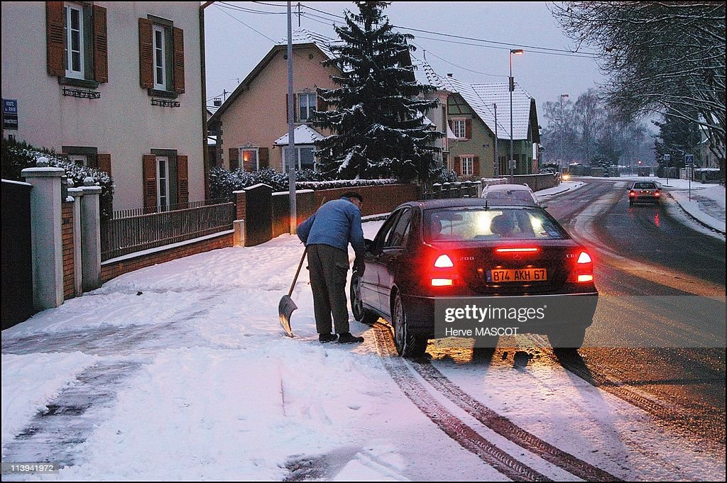Snow and cold weather in eastern France, On January 26, 2006-Erstein, a man removing the snow from his door steps, talks to a car driver in the Bas Rhin region.