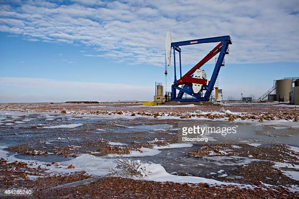 Snow and ice cover the ground near a pumpjack on the site of an oil well outside Williston North Dakota US on Thursday Feb 12 2015 A plunge in global...