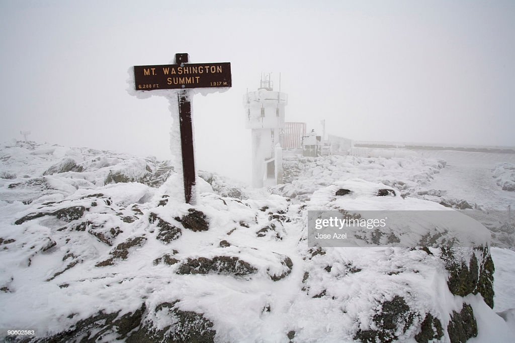 A snow and ice covered sign marks the summit of Mount Washington in the White Mountains of New Hamps