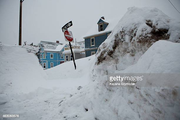 Snow banks from prior snowstorms rise above street signs on the corner of a residential street on February 9 in the Dorchester neighborhood of Boston...