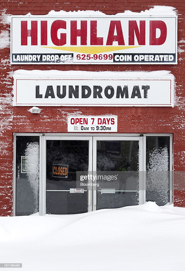 Snow blocks the door of Highland Laundromat, normally open 7 days a week, after Winter Storm Nemo in Somerville, Massachusetts, U.S., on Saturday, Feb. 9, 2013. More than two feet of snow fell on parts of the U.S. Northeast as high winds left hundreds of thousands of people in the region without power, closed highways and forced the cancellation of 4,700 flights. Photographer: Kelvin Ma/Bloomberg via Getty Images